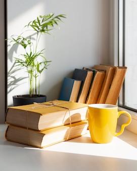Arrangement avec des livres et une tasse
