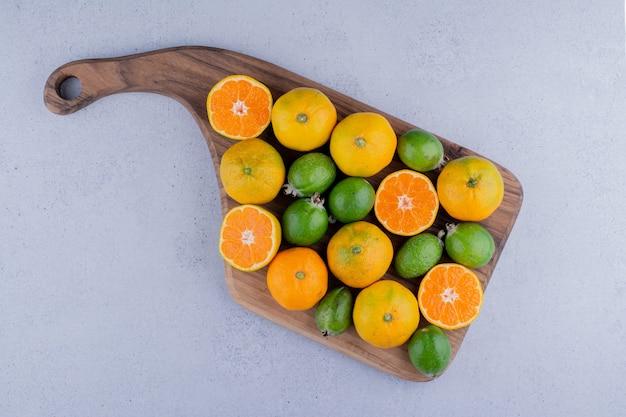 Arrangement de mandarines et feijoas sur une planche sur fond de marbre. photo de haute qualité