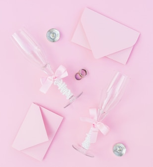 Arrangement de mariage rose avec des verres de champagne et des invitations