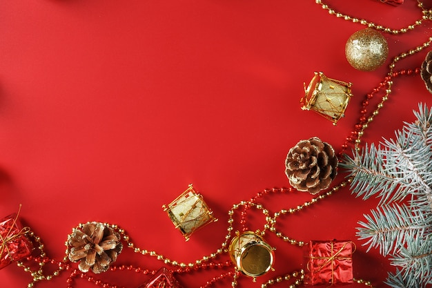 Arrangement de noël d'ornements de noël et de décorations pour arbres de noël sur fond rouge. espace libre pour le texte.