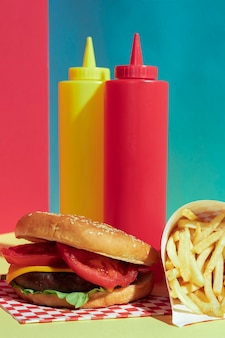 Arrangement de nourriture avec des bouteilles de sauce et un hamburger