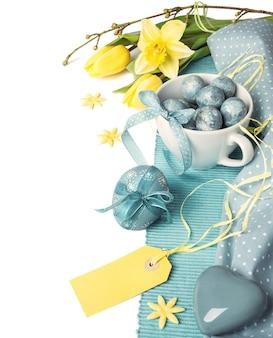 Arrangement de pâques en bleu et jaune avec des fleurs et des décorations