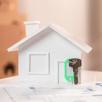 Arrangement avec petite maison blanche et clés