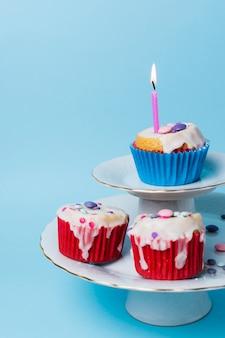 Arrangement de petits gâteaux d'anniversaire vue de face sur fond bleu
