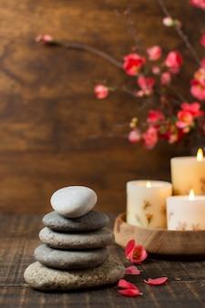 Arrangement avec des pierres de spa et des bougies allumées