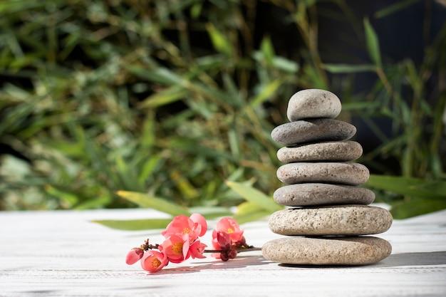 Arrangement avec des pierres de spa et des fleurs