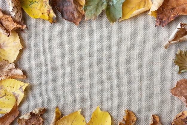 Arrangement plat avec des feuilles sur la texture du sac