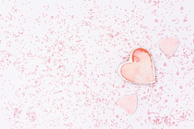 Arrangement plat avec fond en forme de coeur rose et rose