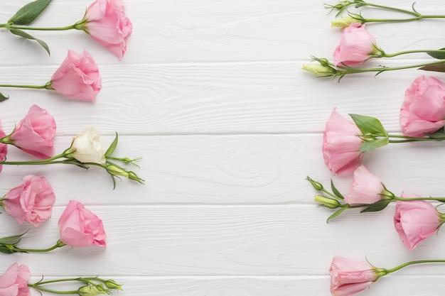 Arrangement plat laïque avec des roses roses sur fond en bois
