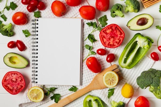 Arrangement plat avec légumes et cahier