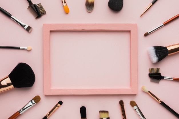 Arrangement à plat avec pinceau à maquillage et cadre rose