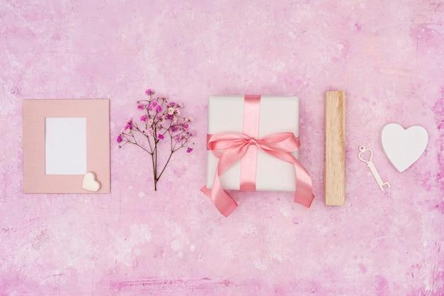 Arrangement plat avec présent sur fond rose