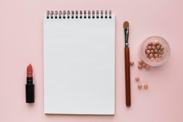 Arrangement à plat avec des produits de maquillage et un cahier