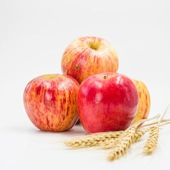 Arrangement avec des pommes rouges et des épis de blé