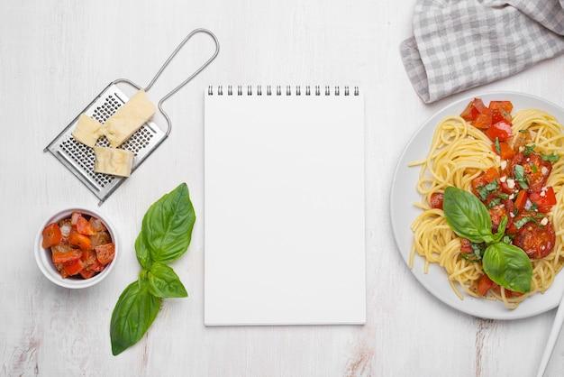 Arrangement de repas de nourriture locale à plat avec bloc-notes