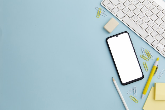 Arrangement stationnaire sur fond bleu avec téléphone et espace copie