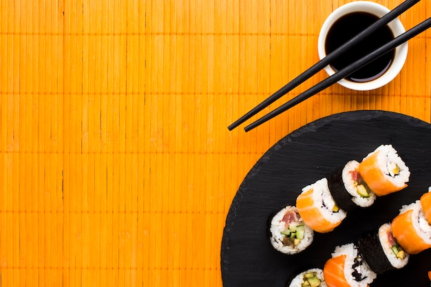 Arrangement de sushis plats sur une natte de bambou orange