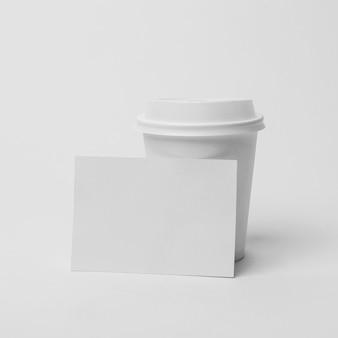 Arrangement avec tasse à café et morceau de papier