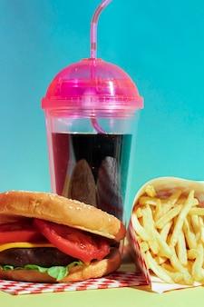 Arrangement avec tasse de jus et cheeseburger savoureux