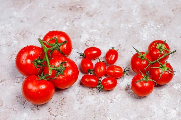 Arrangement de tomates assorties fraîches colorées sur une surface en béton