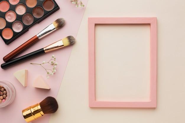 Arrangement de la vue de dessus avec articles de maquillage et cadre