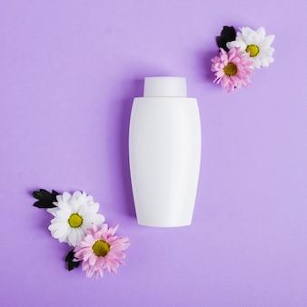 Arrangement de vue de dessus avec une bouteille blanche et des fleurs