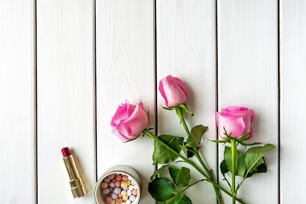 Arrangement de vue de dessus avec maquillage, roses et espace copie sur fond en bois blanc. concept de jour, de beauté et de féminité de la femme.