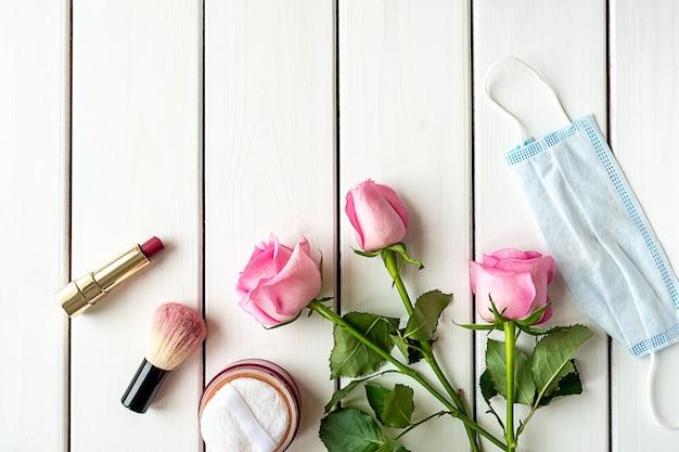 Arrangement de vue de dessus avec maquillage, roses, masque médical et espace copie sur fond en bois blanc. concept de la beauté à l'ère covid-19.