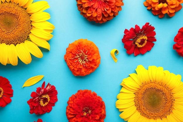 Arrangements de fleurs d'automne faits de tournesols, de feuilles et de fleurs sur fond bleu, vue de dessus. composition créative. vue de dessus