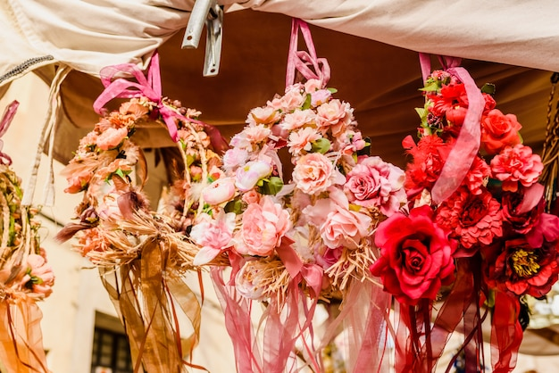 Arrangements floraux suspendus depuis un balcon dans une rue d'une ville méditerranéenne.