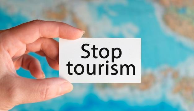 Arrêt du tourisme et fermé - texte sur une feuille blanche avec globe sur l'arrière-plan de la carte de l'atlas