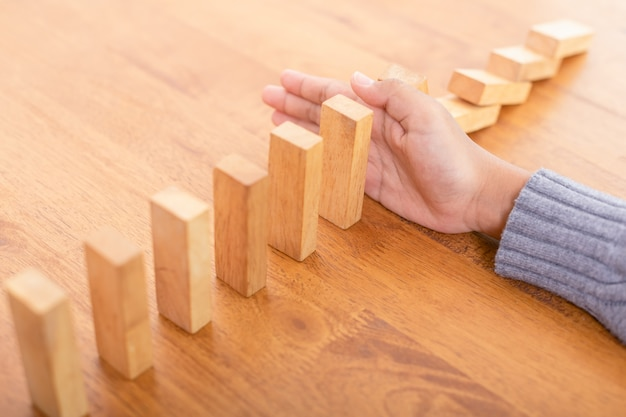 Arrêt manuel du bloc de bois, créant un effet de risque de domino