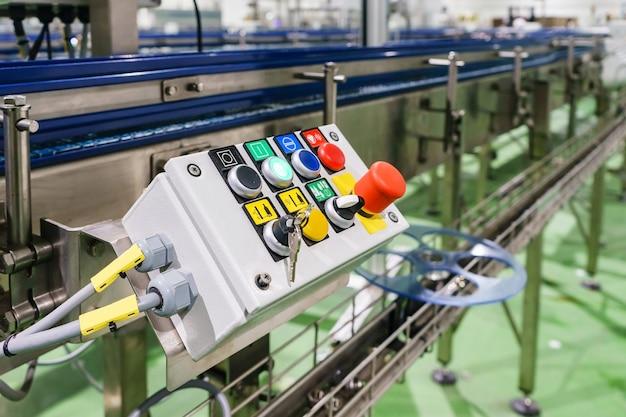 Arrêt d'urgence installé sur le convoyeur en ligne de l'usine de machines, bouton start - stop