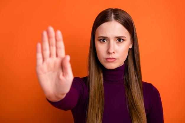 Arrête ne bouge pas. sérieuse confiante fille stricte tenir la main signe bloc de paume manière rejeter la solution en désaccord porter un bon pull isolé sur fond de couleur vibrante