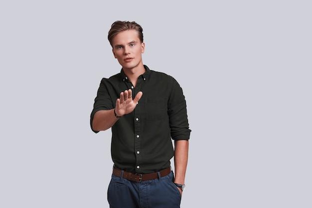 Arrêter! beau jeune homme gardant la main dans la poche et faisant des gestes en se tenant debout sur fond gris