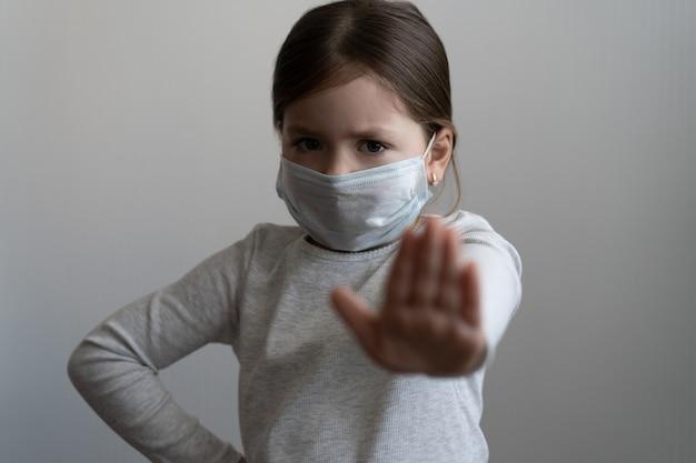 Arrêter le coronavirus ou le concept d'épidémie de covid 19 - une jeune fille au masque de protection médicale montre un geste d'arrêt avec la main - une fille tendue la paume de la main avec peur, concept de quarantaine ou d'isolement à domicile
