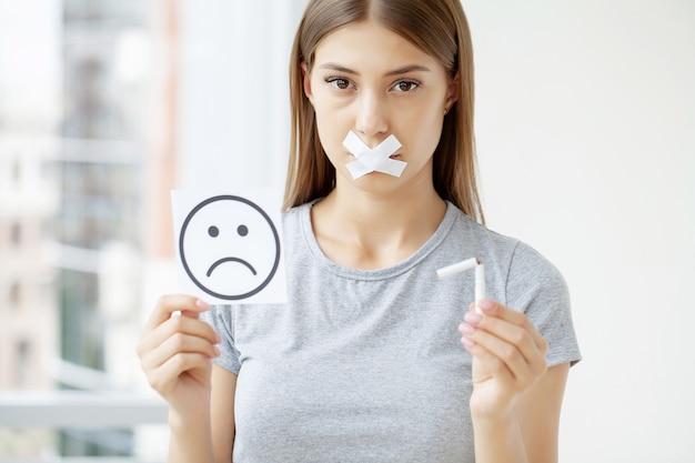 Arrêter de fumer, une femme avec une bouche scellée tenant une cigarette cassée