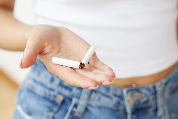 Arrêter de fumer, gros plan d'une femme brisant la cigarette