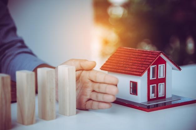 Arrêter à la main le risque que les blocs de bois tombent sur la maison, l'assurance habitation, la sécurité et le concept de gestion des risques.