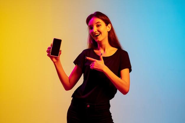 Arrêter le portrait d'une jeune femme caucasienne sur fond de studio bleu-jaune dégradé en néon