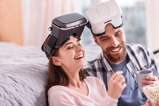 Arrêter de rire. jolly couple agréable et attrayant dans des lunettes vr nickering tout en posant sur l'arrière-plan flou et en parlant