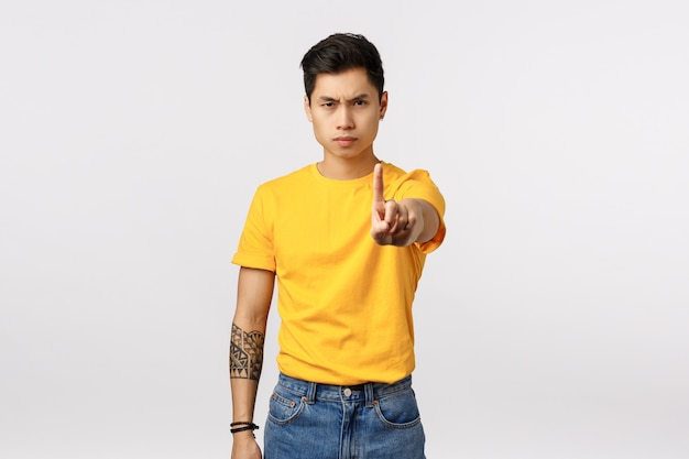 Arrêtez ça. sérieux et déterminé jeune beau mec asiatique avec des tatouages, étendre le bras et secouer l'index tabou, interdire ou interdire le geste, froncer les sourcils, mur blanc
