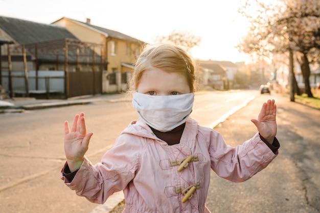 Arrêtez le coronavirus et les maladies épidémiques virales. enfant en bonne santé dans un masque de protection médical montrant l'arrêt du geste. protection et prévention de la santé pendant la grippe et les flambées infectieuses. enfant dans la rue.
