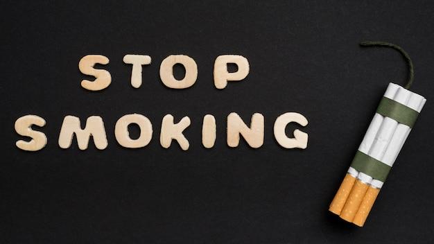Arrêtez de fumer le texte avec un tas de cigarettes disposées sur un fond noir