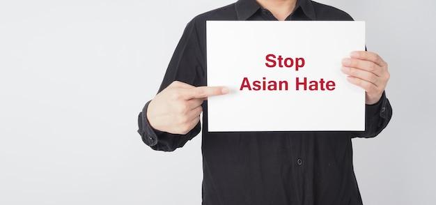 Arrêtez la haine asiatique en rouge, écrivez sur du papier à tableau blanc. un homme asiatique porte une chemise noire tenant du papier sur fond blanc.