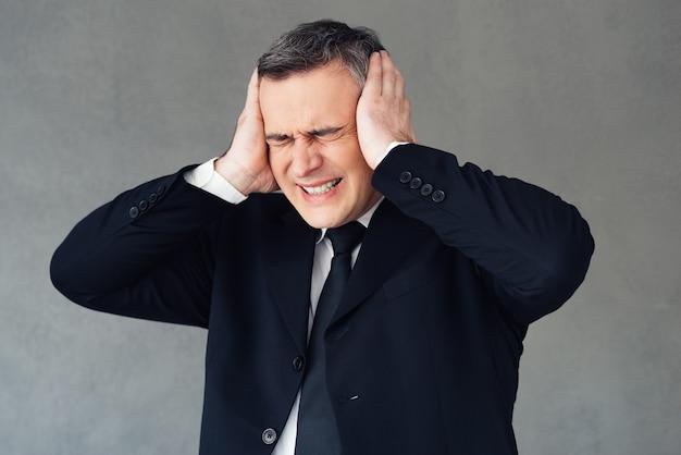 Arrêtez-le immédiatement ! homme d'affaires mûr ayant l'air frustré et couvrant les oreilles avec ses mains en se tenant debout sur fond gris