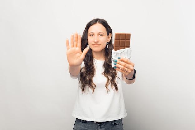 Arrêtez de manger du chocolat, dit une jeune femme en faisant des gestes et en tenant une barre.