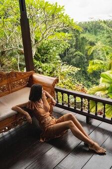Arrêtez le moment. jeune femme détendue étant seule dans un bungalow, regardant des palmiers pour s'inspirer