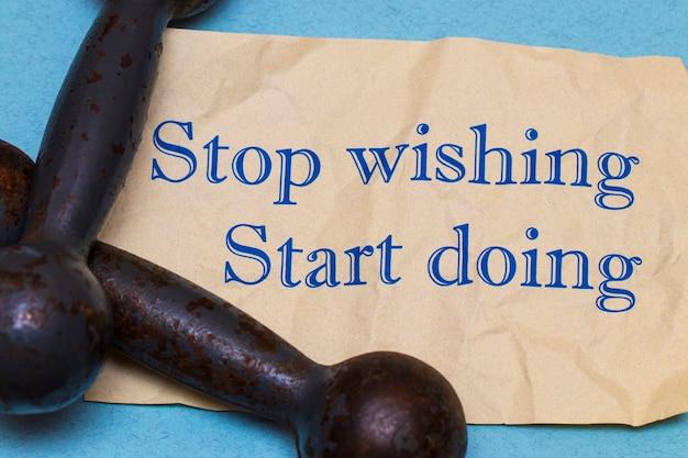 Arrêtez de souhaiter, commencez à faire ! expression de motivation sur une feuille de papier avec des haltères et un ruban à mesurer sur fond bleu