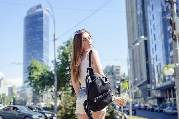 Arrière arrière derrière vue rapprochée photo portrait d'une jolie femme séduisante portant un t-shirt débardeur blanc regardant la caméra tenant une tasse à la main des bâtiments modernes sur fond